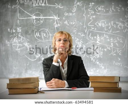 Teacher sitting in a classroom - stock photo
