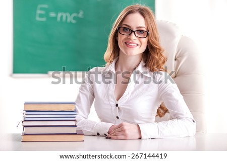 Teacher sitting in the classroom on blackboard background. - stock photo