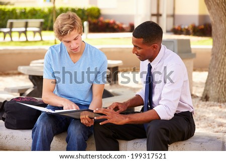 Teacher Sitting Outdoors Helping Male Student With Work