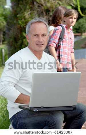 Teacher sitting outside with laptop computer - stock photo