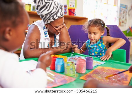 Teacher sitting with kids in a preschool class, close up - stock photo