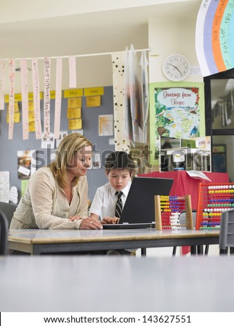 Teacher sitting with schoolboy using laptop in classroom - stock photo