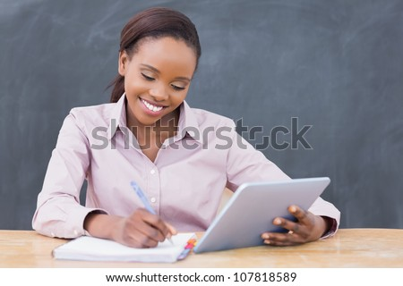 Teacher smiling while holding a tablet computer in a classroom - stock photo
