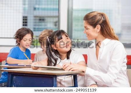 Teacher speaking to asian student while classmates writing on background. - stock photo