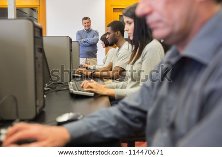Teacher standing at front of computer class with arms crossed - stock photo