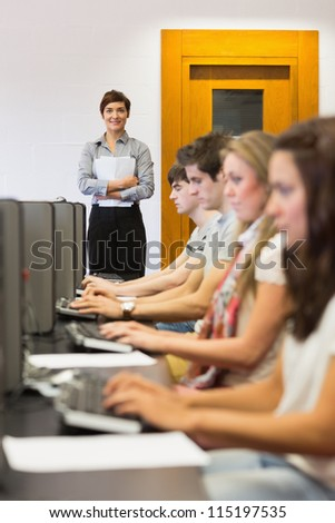 Teacher standing holding paper while smiling in computer room in college - stock photo