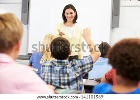 Teacher Standing In Front Of Class Asking Question - stock photo