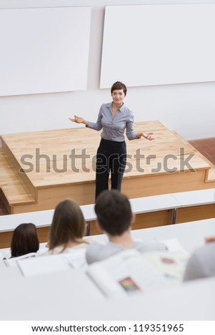 Teacher standing while talking to the students - stock photo