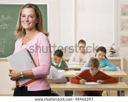 Teacher standing with notebook in classroom - stock photo