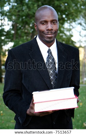 Teacher stands with books before class at college - stock photo