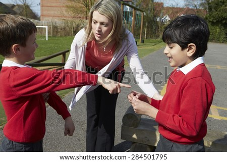 Teacher Stopping Two Boys Fighting In Playground - stock photo