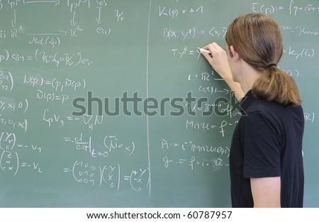 teacher / student writing math formulas on the chalkboard - stock photo