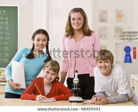Teacher, students and microscope in classroom - stock photo