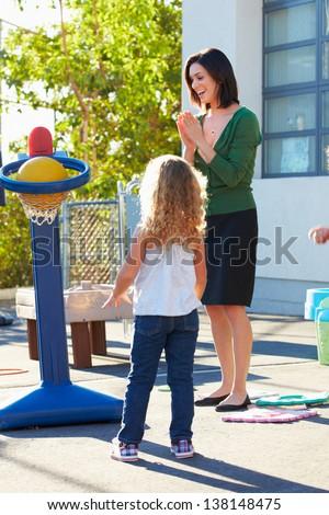 Teacher Supervising Breaktime At Elementary School - stock photo