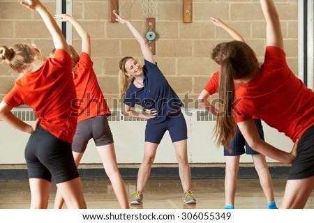 Teacher Taking Exercise Class In School Gym - stock photo