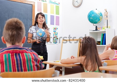 Teacher talking about Earth globe, while children is attending her - stock photo