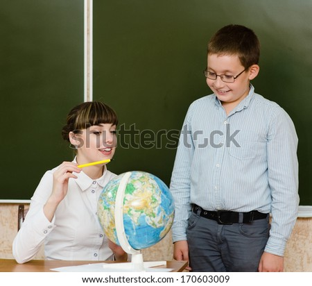 Teacher teaches boy showing Globe - stock photo