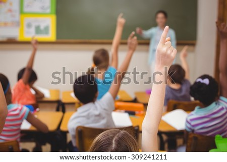 Teacher teaching a lesson in class at the elementary school - stock photo