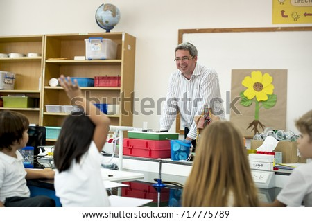Teacher teaching flower structure to diverse group of kindergarten students in science class
