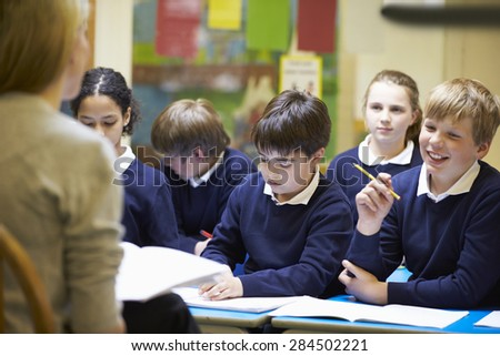 Teacher Teaching Lesson To Elementary School Pupils - stock photo