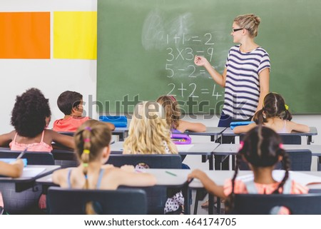 Teacher teaching mathematics to school kids in classroom at school