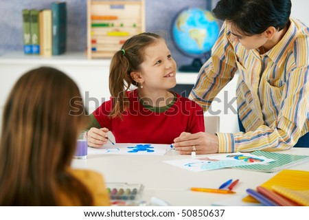 Teacher teaching painting to elementary age children in classroom at primary school. - stock photo