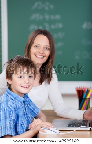 Teacher teaching young cheerful student from laptop in the classroom - stock photo