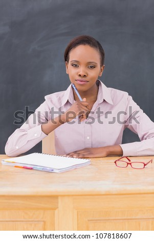 Teacher thinking while looking at camera in a classroom