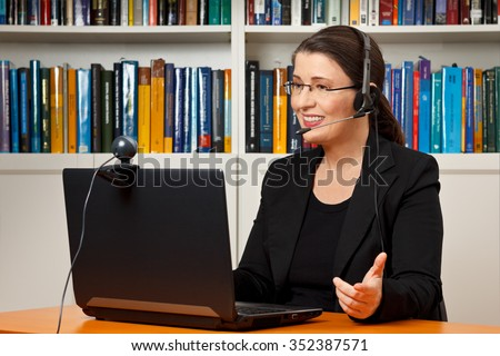 Teacher, tutor or professor with headset, laptop and camera in her office explaining something at an online lesson or video lecture, webinar - stock photo
