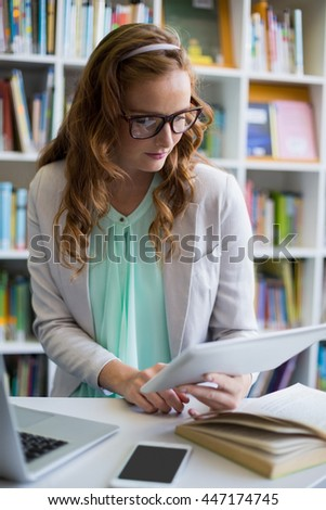 Teacher using digital tablet with laptop and phone on table in library at school - stock photo
