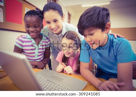 Teacher using laptop with pupils at the elementary school - stock photo