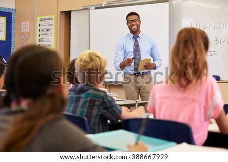 Teacher using tablet computer in an elementary school class - stock photo