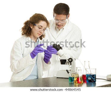 Teacher watches as a college or high school student prepares a slide for viewing under a microscope.  White background - stock photo