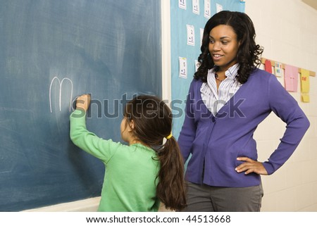 Teacher watching young female student write on blackboard. Horizontally framed shot. - stock photo
