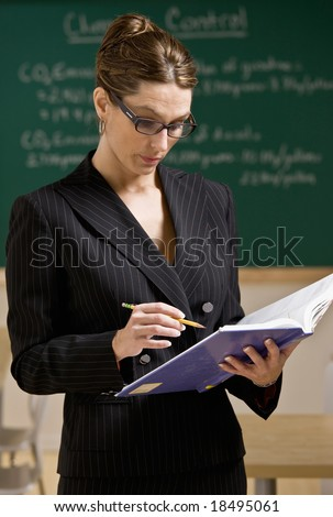 Teacher wearing eyeglasses reading text book in school classroom
