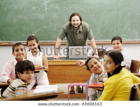 Teacher with children in classroom using laptop, boys and girls in school together learning