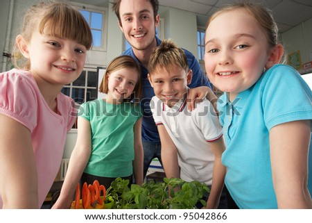 Teacher with children learning about plants - stock photo