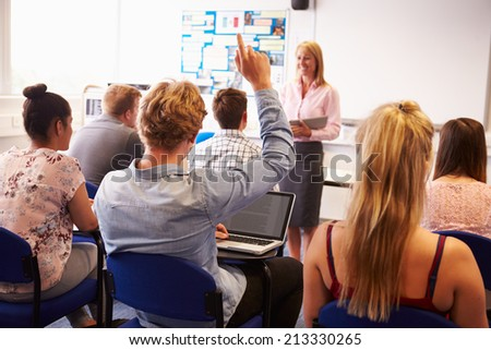 Teacher With College Students Giving Lesson In Classroom - stock photo