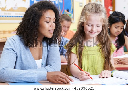 Teacher With Female Elementary School Pupil In Class - stock photo