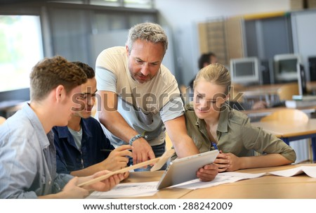 Teacher with group of students working on digital tablet