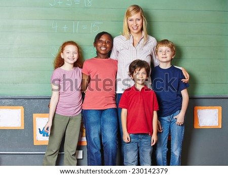 Teacher with her class of students in elementary school in front of a chalkboard