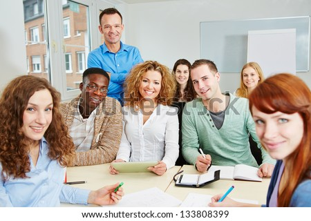 Teacher with his happy students in a college course classroom - stock photo