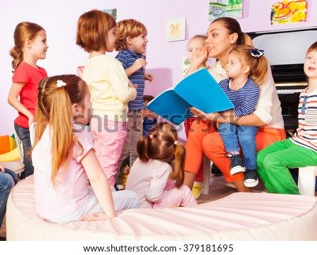 Teacher with kids read and discuss book - stock photo
