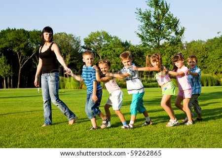 Teacher with kids walking to the city park - stock photo