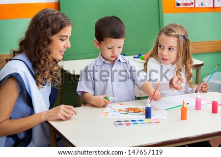 Teacher with little children painting at desk in classroom - stock photo