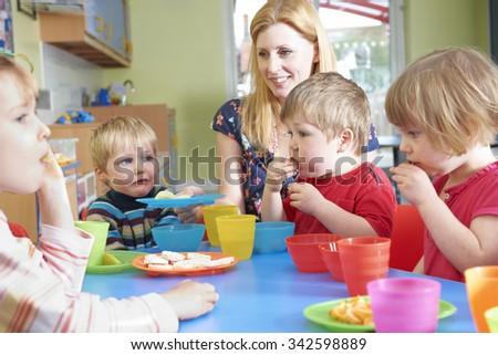 Teacher With Pre School Children Eating Healthy Snacks At Breakt - stock photo