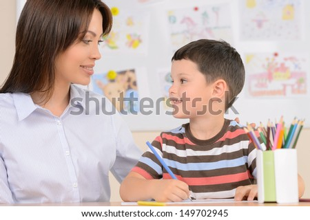 Teacher with pupil. Cheerful schoolboy drawing something something in note pad while sitting near his teacher - stock photo