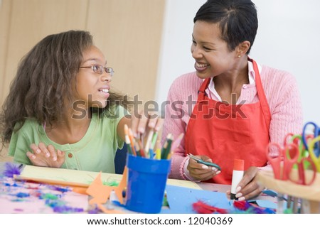 Teacher with pupil in art class - stock photo