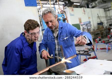 Teacher with student in metallurgy workshop - stock photo