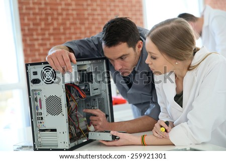 Teacher with student in technology repairing computer - stock photo